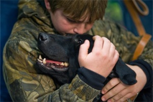 Brady Rusk, 12, hugs Eli, the bomb-sniffing military working dog his older brother Marine Pfc. Colton Rusk, worked with before being killed in action in Afghanistan. Photo courtesy U.S. Air Force photo/Tech. Sgt. Bennie J. Davis III